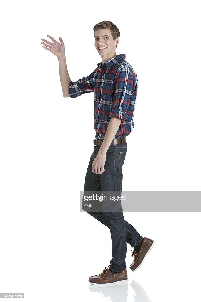 Happy young man waving his hand
