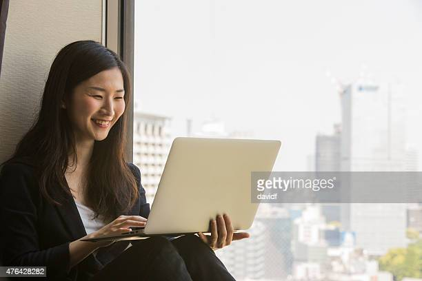 Happy young modern Japanese woman sitting using a laptop computer