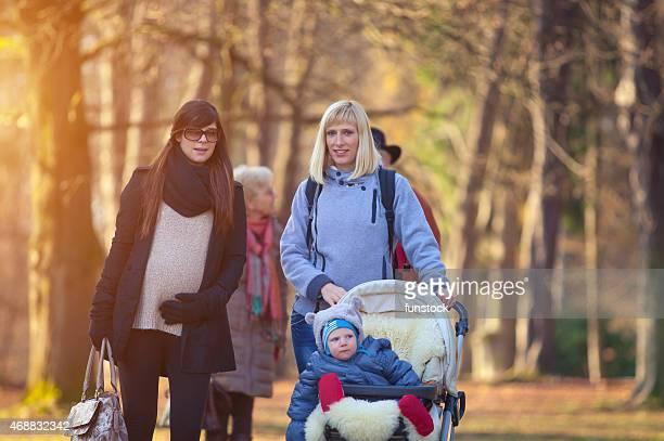 Glückliche junge Mutter mit Kind mit Freund auf den park