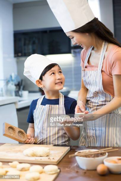 Happy young mother and son baking together