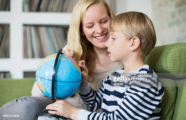 Happy young mother and son looking at globe