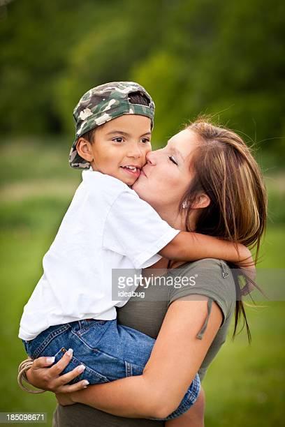 Heureuse jeune mère tenant et d'embrasser Son fils en plein air