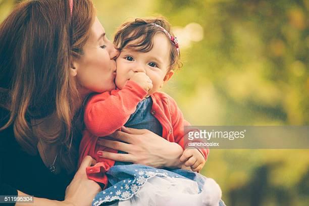 Jeune mère embrassant son bébé fille