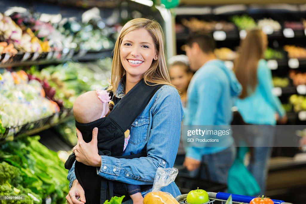 Happy young mother shopping for groceries with baby