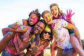 happy young multiethnic friends with colorful paint on clothes having fun together at holi festival