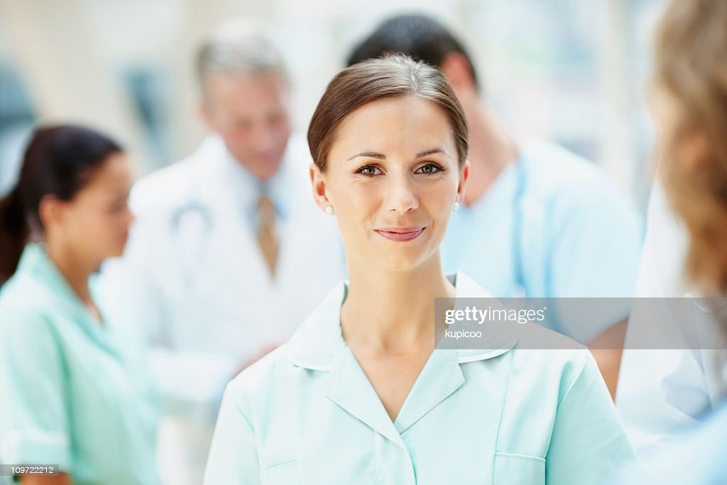 Happy young nurse with her blur medical team in background : Stock Photo