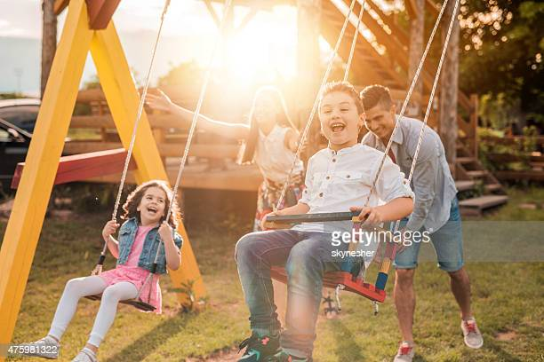 Happy young parents swinging their children at sunset.