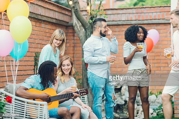 Heureux jeunes danser et chanter au Backyard fête.