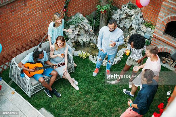 Happy Young People Dancing And Singing At Backyard Party.