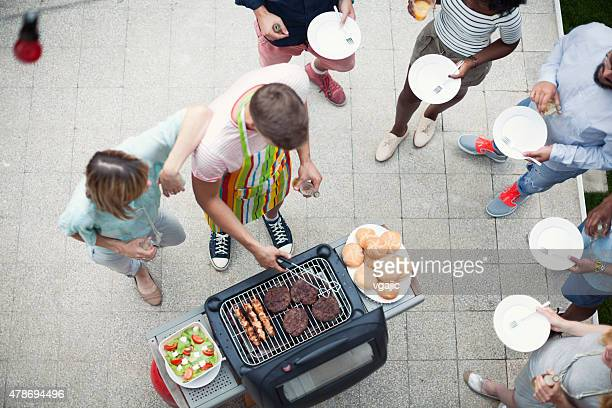 Happy Young People Eating At Barbecue Party.
