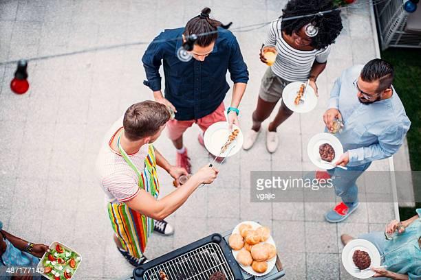 Glückliche junge Menschen Essen im Barbecue-Party.