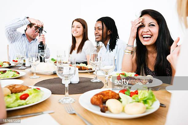 Happy young people gathered round dining table