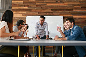 Group of happy young people having a business meeting. Creative people sitting at table in boardroom with man explaining business strategy.