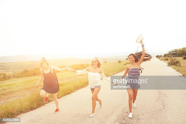 Happy young people holding hands and dancing on the road