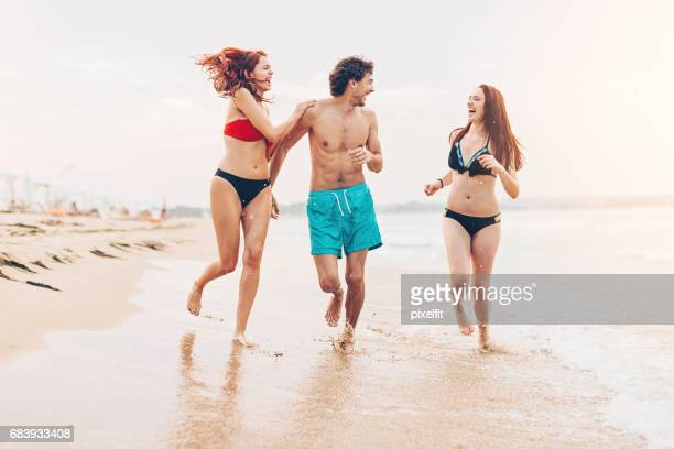 Happy young people in swimwear on the beach