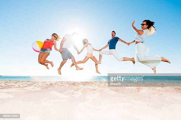 Happy young people jumping on the beach.
