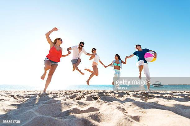 Glückliche junge Menschen springen am Strand.