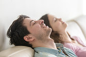 Side view of happy young couple enjoying lying on sofa at home, relaxing with eyes closed, recreating, dreaming of vacation, meditating and resting, listening to music, imagining, leisure lazy day