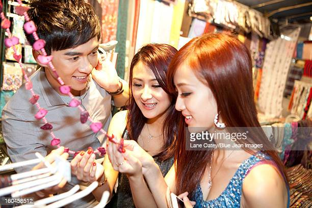 Happy young people shopping on Temple Street of Hong Kong, night view