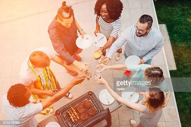 Glückliche junge Menschen beim Anstoßen an Barbecue-Party.