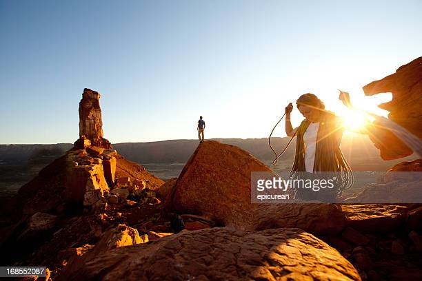 Happy young rock climber coiling her rope at sunset