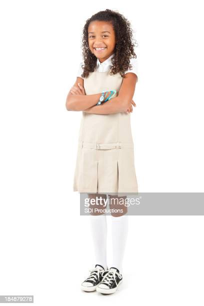 Happy young school girl in uniform with arms crossed