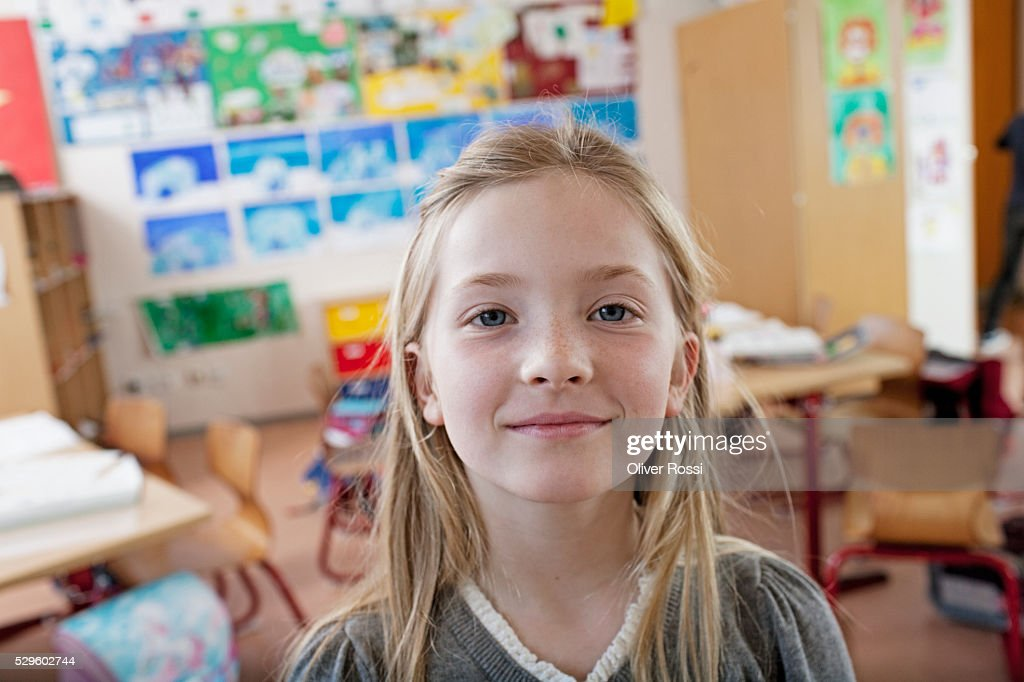 Happy young school girl (8-9) posing in classroom : Stockfoto
