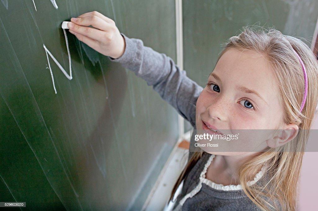 Happy young school girl (8-9) writing on blackboard : Stock Photo