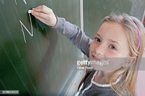 Happy young school girl (8-9) writing on blackboard : Foto de stock