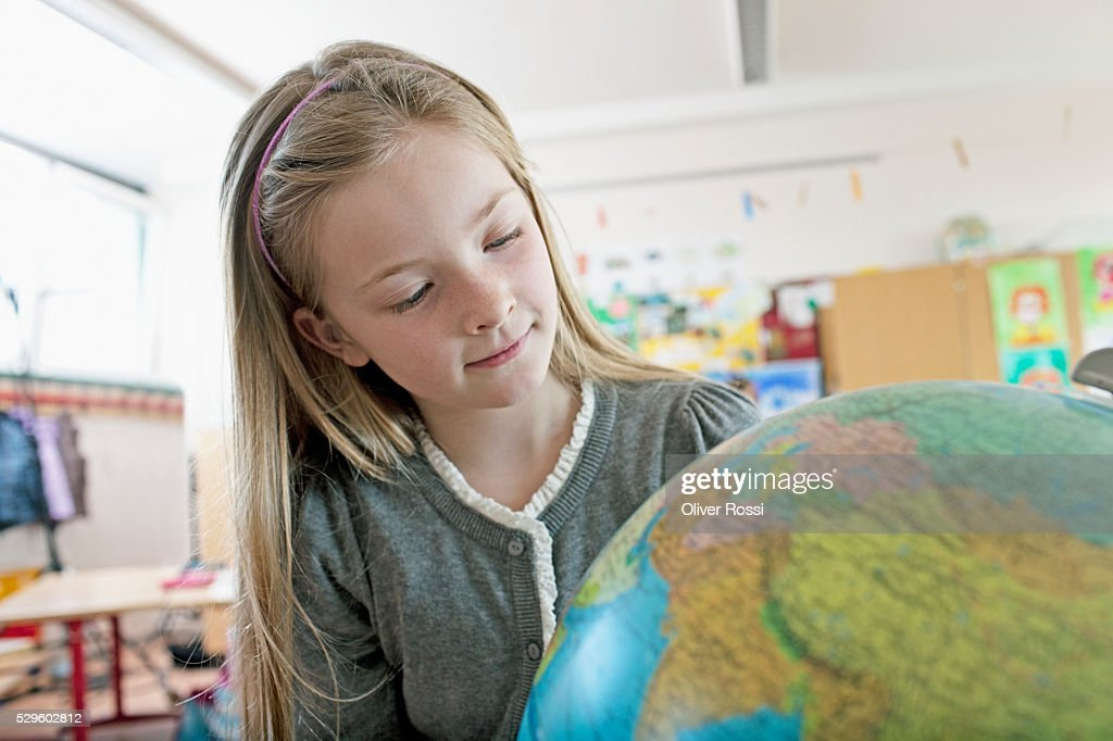 Happy young schoolgirl (8-9) looking at globe : Stock Photo