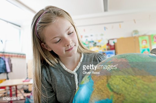 Happy young schoolgirl (8-9) looking at globe : Foto de stock