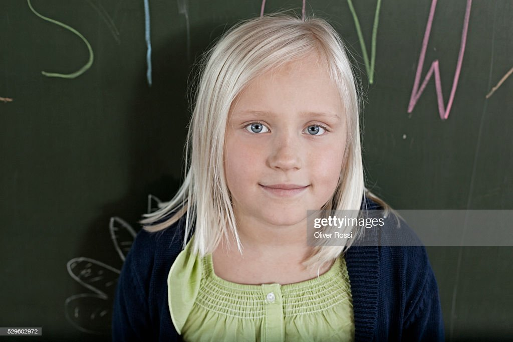 Happy young schoolgirl (8-9) posing against blackboard : Stock Photo