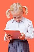 Happy young schoolgirl using tablet PC over orange background