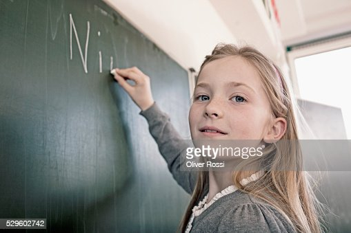 Happy young schoolgirl (8-9) writing on blackboard : Stock-Foto