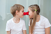 Happy young siblings in white tshirts rubbing clown noses against each other