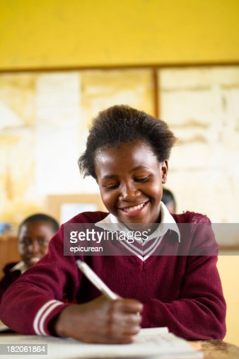 Happy young South African girl studying in a rural classroom