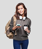 Happy young tourist girl holding smartphone and coffee