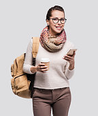 Smiling traveler woman using smart phone and holding coffee cup