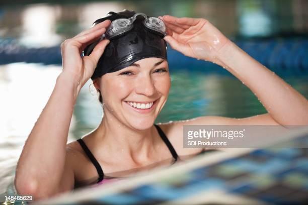 幸せな若い水泳ゴーグルでパッティングのプール