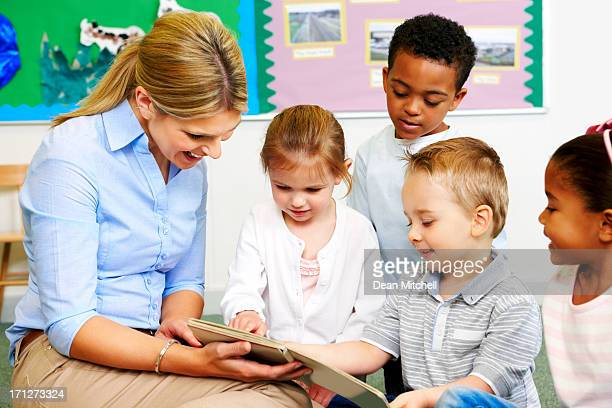 Happy young teacher and preschooler reading storybook