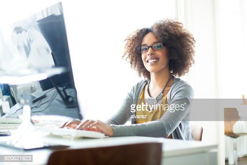 Happy young trainee working on computer