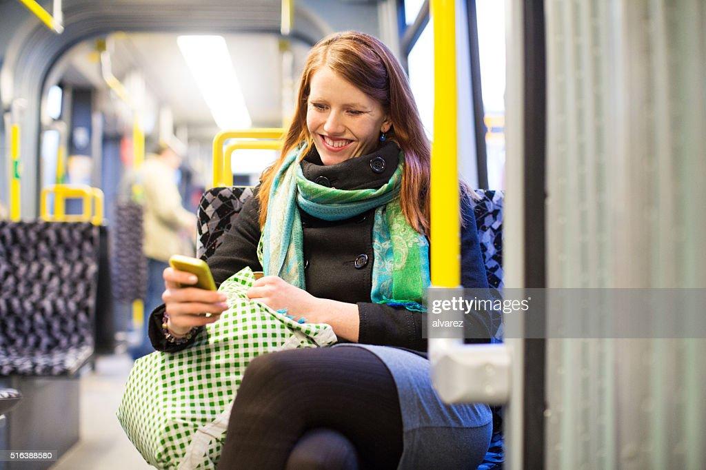 Glückliche junge Sie per U-Bahn mit Mobiltelefon : Stock-Foto