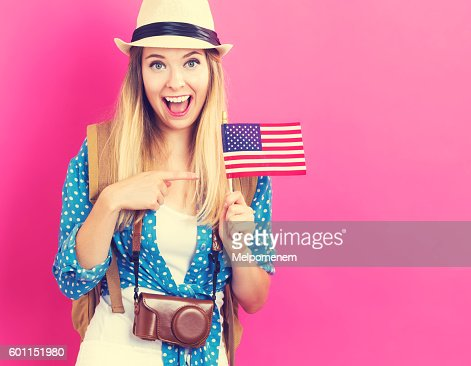 Happy young traveling woman holding American flag : Stock Photo