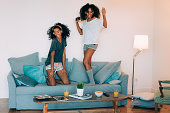 """Happy young two black women sitting and standing up in the couch on the computer and mobile phone with headphones dancing """"n"""