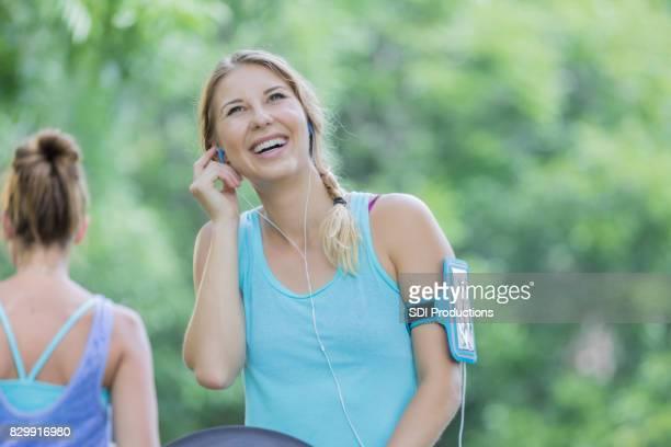 Heureux jeune femme ajuste écouteurs avant d'exercer