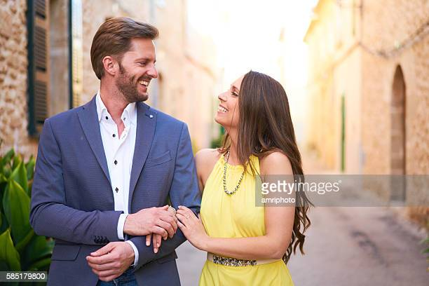 happy young woman and man walking in town