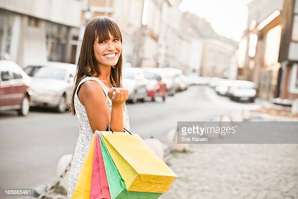 Happy young woman and shopping bags on city street