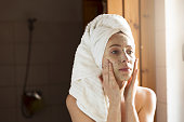 Happy young woman applying face mask in bathroom. Beautiful female in front of mirror doing beauty treatment.
