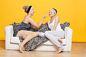 Happy young woman applying face pack on friend's face while sitting on sofa against yellow wall