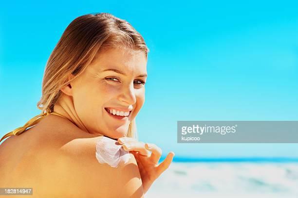 Glückliche junge Frau benutzt Sonnencreme an einem sonnigen Tag